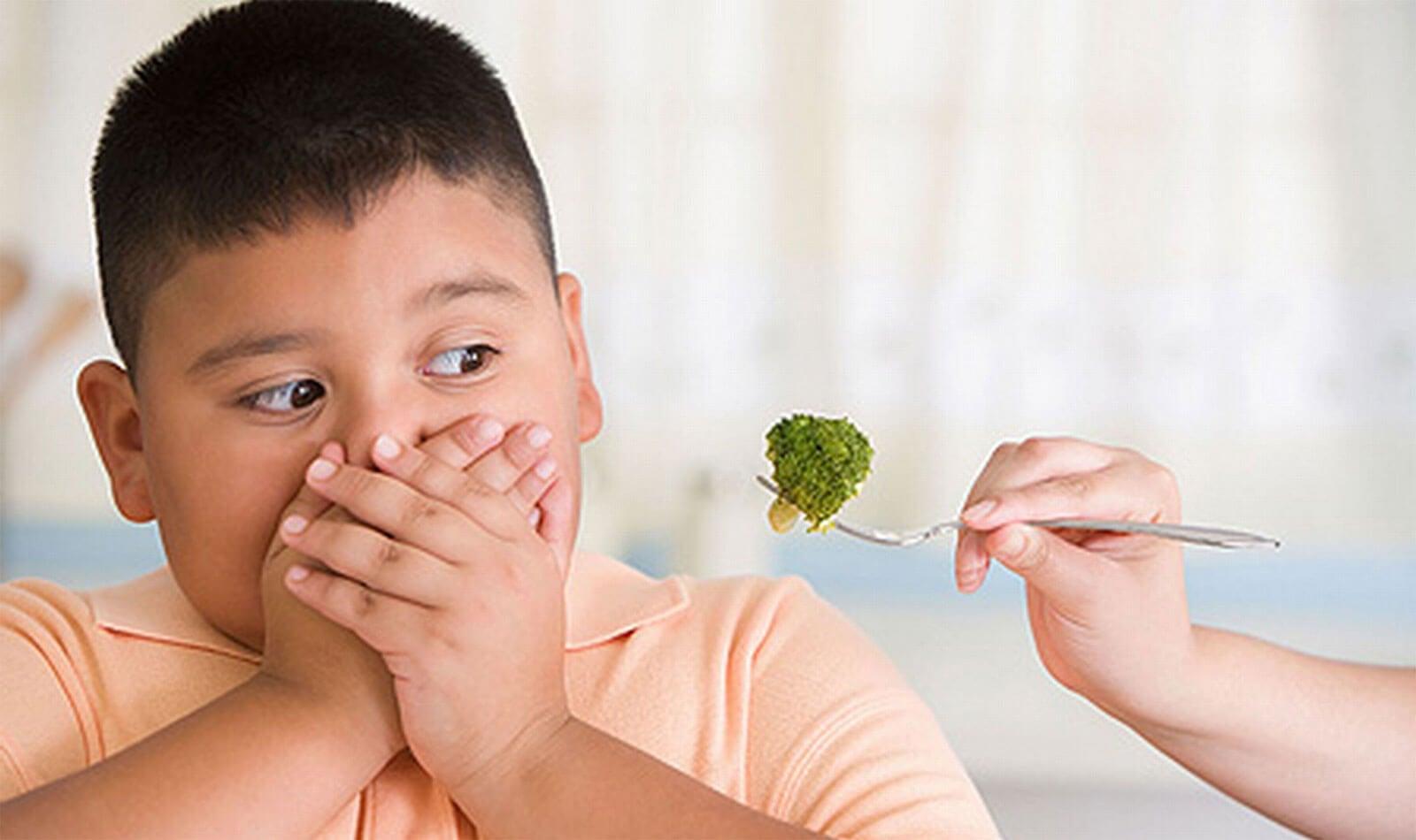Niño con obesidad infantil rechazando un trozo de brócoli