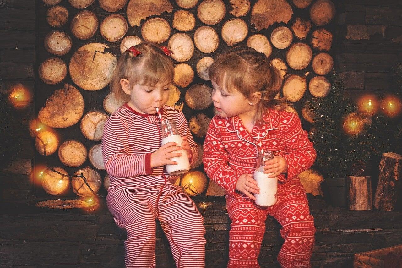 Dos niñas en pijama bebiendo leche.